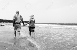 20667296-happy-senior-couple-walking-together-on-a-beach-couple-elderly-old